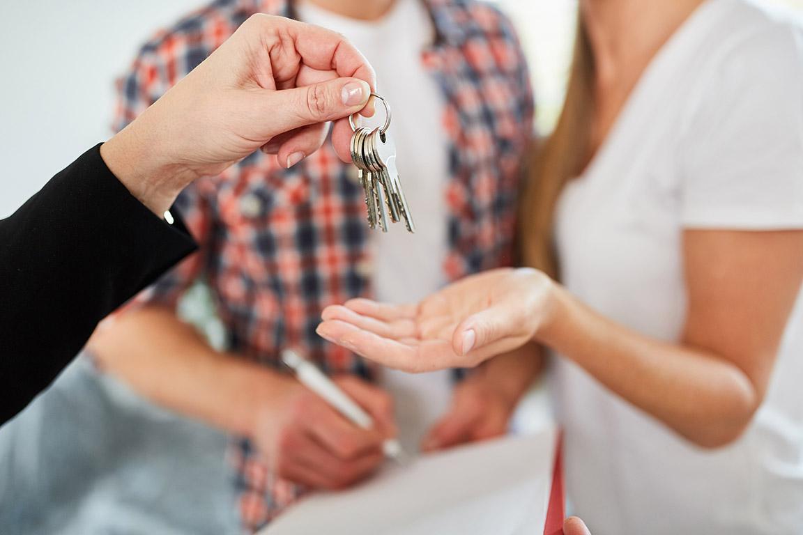 dieses Foto zeigt Personen bei einer Schlüsselübergabe